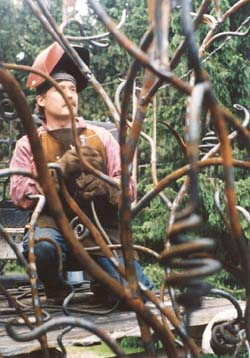 A younger Ken Roby working on an iron sculpture.