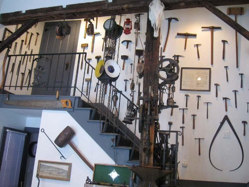 A collection of antique smithing tools displayed on a wall.